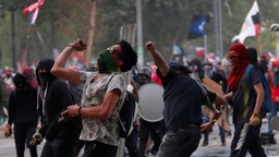 Vermummte Demonstranten bei den Protesten in Santiago de Chile | Bildquelle: REUTERS