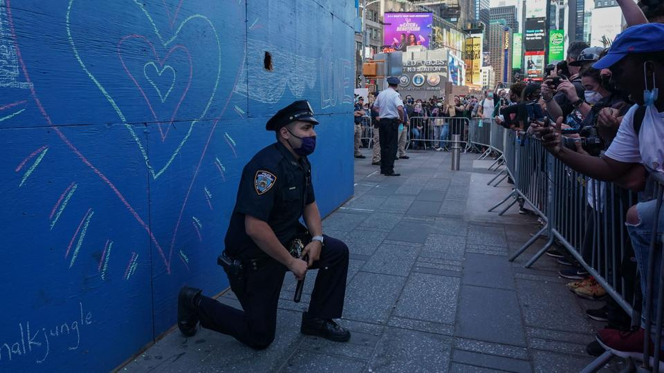 Ein Polizist kniet vor Demonstranten in New York. | Bildquelle: AFP