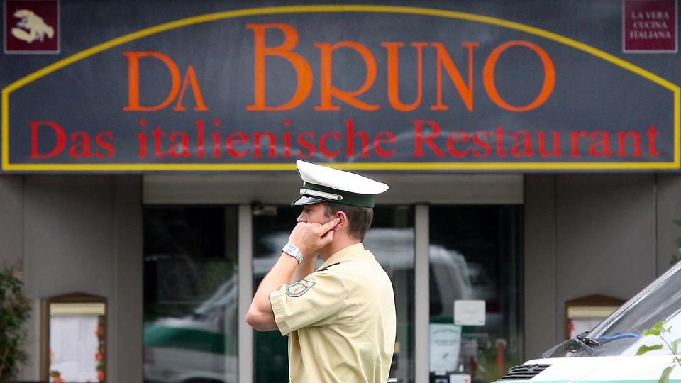 "Ein Polizist telefoniert am 15.08.2007 in Duisburg am Schild des Restaurants ""Da Bruno"" in der Nähe des Tatortes, wo am Morgen fünf Menschen erschossen und ein Mann schwer verletzt aufgefunden worden waren. 