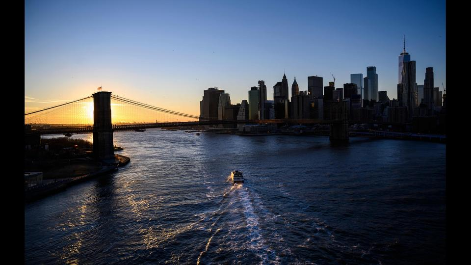 Sonnenuntergang hinter der Brooklyn Bridge neben der Skyline von Manhattan in New York City. | Bildquelle: AFP