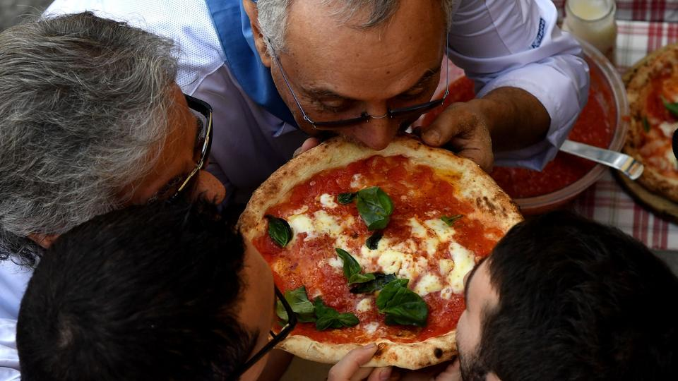 Pizzabäcker in Neapel beißen in eine Pizza Margherita. | Bildquelle: AFP