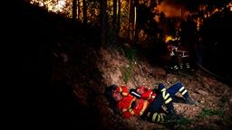 Firefighters rest during a wildfire at Penela, Coimbra, central Portugal, on June 18, 2017.  A wildfire in central Portugal killed at least 25 people and injured 16 others, most of them burning to death in their cars, the government said on June 18, 2017. Several hundred firefighters and 160 vehicles were dispatched late on June 17 to tackle the blaze, which broke out in the afternoon in the municipality of Pedrogao Grande before spreading fast across several fronts.