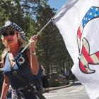 Eine Frau mit einer QAnon-Flagge besucht das Mount Rushmore National Monument in Keystone, South Dakota, USA | AFP